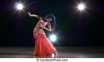 Beautiful girl dancing belly dance, on black, back light, slow motion