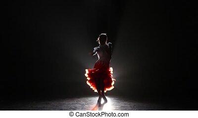 Beautiful girl dancing cha-cha-cha in the studio on a dark background, smoke, silhouette