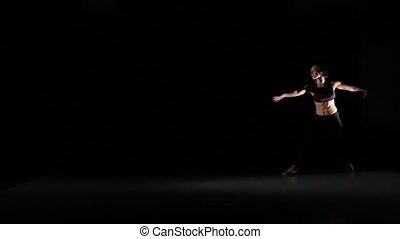 Beautiful girl dancing contemp in the shadow on black background, slow motion