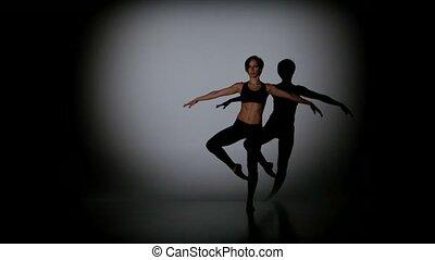Beautiful girl dancing contemp on a black background, spot light