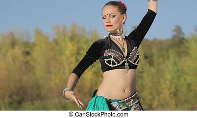 Beautiful  girl dancing exotic dance on nature