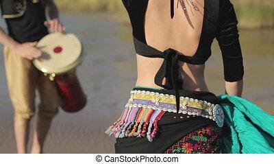 Beautiful  girl dancing exotic dance with drummer