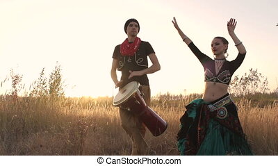 Beautiful  girl dancing exotic dance with drummer