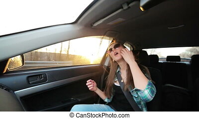Beautiful girl dancing in the car, sunset