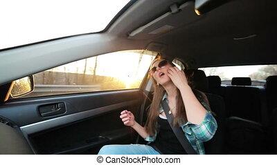 Beautiful girl dancing in the car, sunset