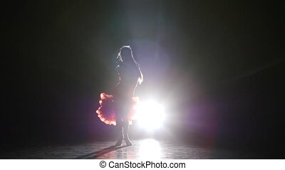 Beautiful girl dancing latin in the studio on a dark background, smoke, silhouette