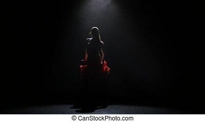 Beautiful girl dancing rumba in the studio on a dark background, smoke
