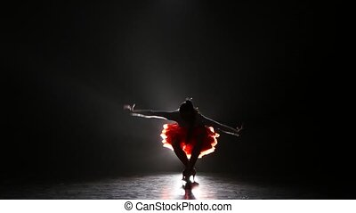 Beautiful girl dancing rumba in the studio on a dark background, smoke, silhouette