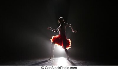 Beautiful girl dancing rumba in the studio on a dark background, smoke, with white backlight