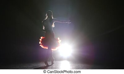 Beautiful girl dancing samba in the studio on a dark background, smoke, silhouette