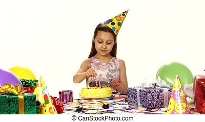 Beautiful girl decorates a cake with candles. On the table are arranged gifts