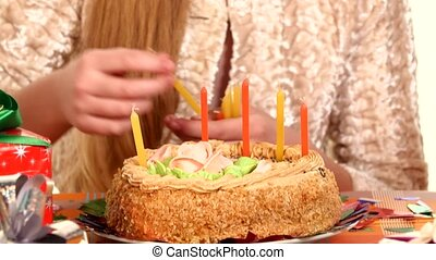 Beautiful girl decorates a cake with candles. The camera moves from top to bottom. close up