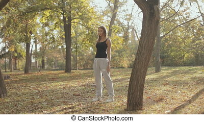 Beautiful girl doing fitness in a park in autumn