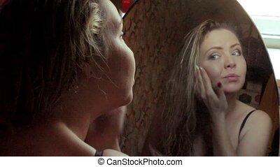 Beautiful girl doing morning makeup near the mirror