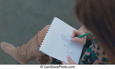Beautiful girl drawing the anchor in pencil while sitting at the port