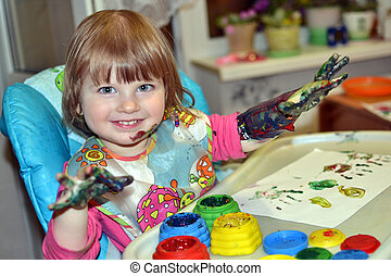 beautiful girl draws with finger paints