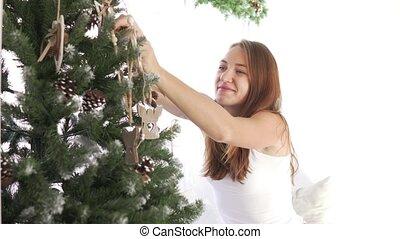 Beautiful girl dress up a christmas tree.