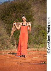 Beautiful girl dressed  terracotta dress with a scarf in her hands