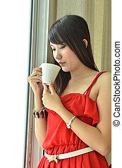 Beautiful girl drinking coffee in front of window