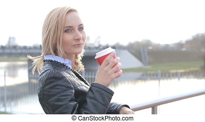 Beautiful girl drinking coffee on the street looking at the camera