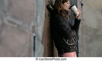 Beautiful girl drinking coffee on the street