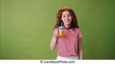 Beautiful girl drinking orange juice and smiling on green...