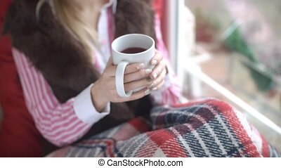 Beautiful girl drinking tea on the windowsill, close-up