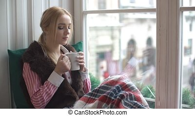 Beautiful girl drinking tea on the windowsill.