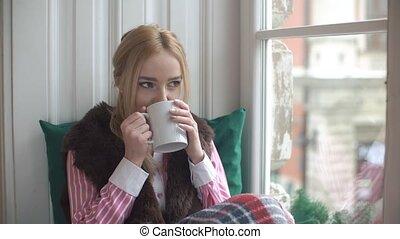 Beautiful girl drinking tea on the windowsill