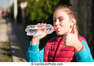 Beautiful girl drinking water after jogging in outdoor