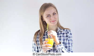 Beautiful girl drinks freshly squeezed orange juice through...