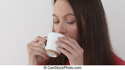 Beautiful girl drinks from white cup - Cute girl takes sip...