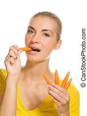 Beautiful girl eating carrot