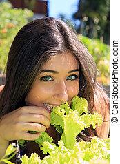 Beautiful girl eating lettuce
