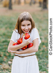 Beautiful Girl Eating Organic Apple in the Orchard. Harvest Concept. Garden, Toddler eating fruits at fall harvest. Apple pie