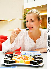 Beautiful girl eating sushi in a restaurant