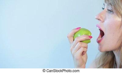 beautiful girl eats a green apple on a blue