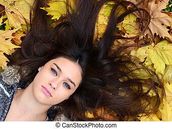 Beautiful girl enjoying nature in autumn forest