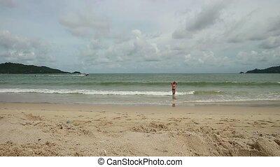 Beautiful girl enjoying summer beach holidays comes into the sea. Travel vacation of happy woman in bikini