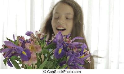 Beautiful girl enjoys bouquet of irises and alstroemeria. -...