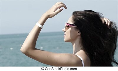 Beautiful girl enjoys the sun on the background of the sea...