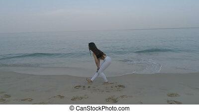 Beautiful girl exercising on the sandy beach