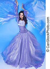 Beautiful Girl . Fashion woman in Blowing Dress Flying