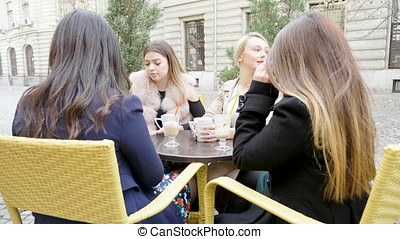 Beautiful girl friends hanging out in the city at cafe terace