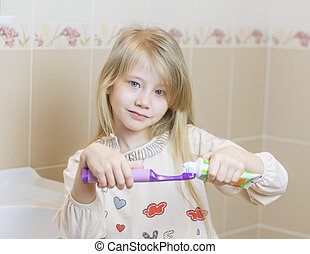 Beautiful girl gets toothpaste on an electric toothbrush.