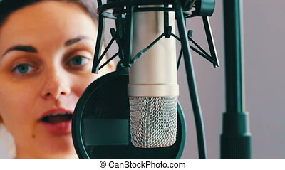Beautiful girl gives an interview in studio microphone -...