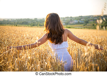 girl goes through a field at sunset