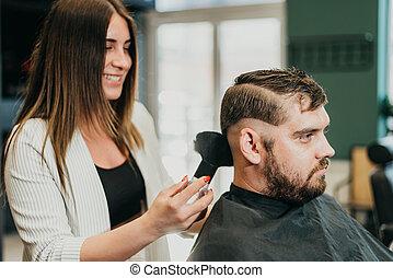beautiful girl hairdresser cuts a bearded man in the salon