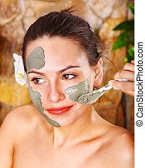 Beautiful girl having clay body mask.