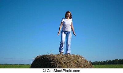 girl having fun dancing in a haystack